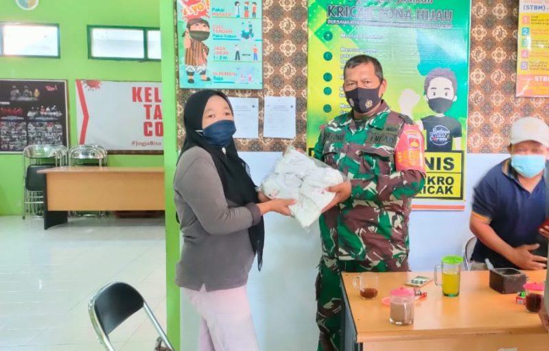 Serma Hartono secara simbolis berikan masker kepada Ketua RT. FOTO: nyatanya.com/istimewa