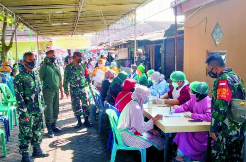 Prajurit Koramil Gamping lakukan pengamanan proses vaksin di Pasar Gamping. FOTO: nyatanya.com/istimewa