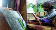 Perupa Agus Merapi menyelesaikan lukisan pandemi di koper kuno. (Foto:nyatanya.com/Humas Magelang)