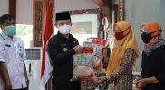 Bupati Kebumen Arif Sugiyanto secara simbolis menyerahkan beras bantuan kepada masyarakat terdampak PPKM Darurat. (Foto:nyatanya.com/Diskominfo Kebumen)