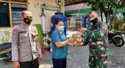 Serma Hartono menyerahkan bantuan beras kepada warga Kricak. (Foto : dokumentasi Koramil 02/Tegalrejo)