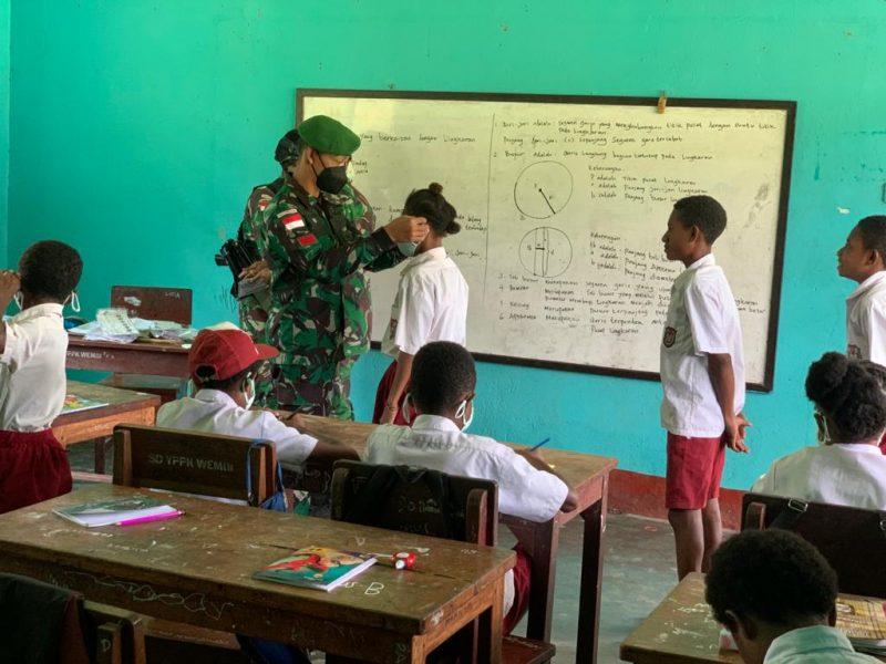 Prajurit Yon 512/QY bagikan masker kepada siswa SD YPPK.  (Foto: Penerangan Yon 512/QY)