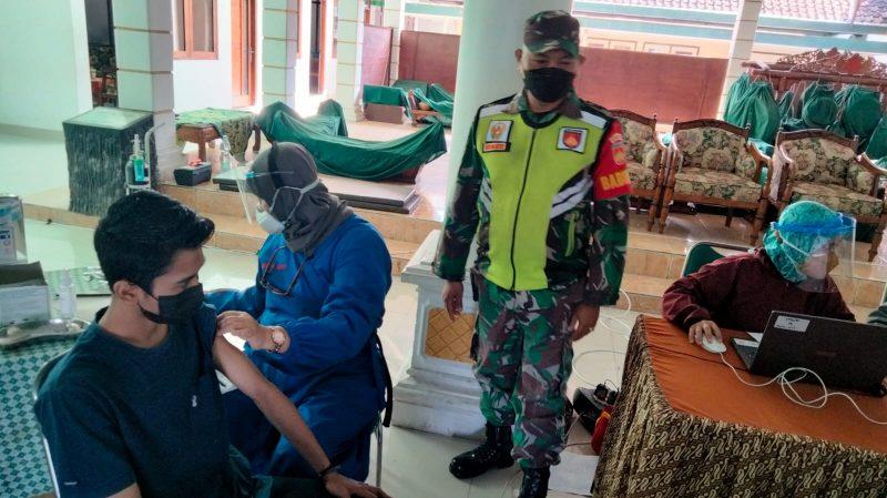 Serma Acip berikan pendampingan saat pelaksanaan vaksinasi tahap dua di Kelurahan Balecatur.  (Foto: dokumentasi Koramil Gamping)