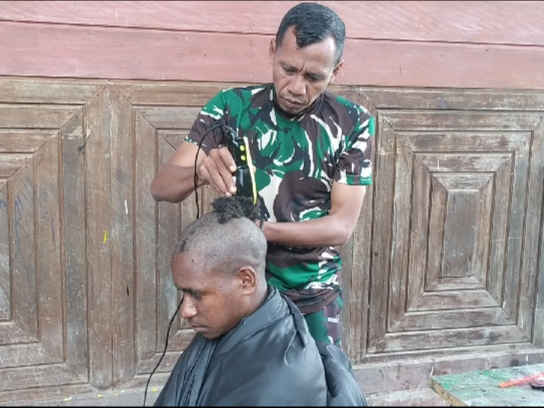 Prajurit Yon 403/WP sedang mencukur rambut pemuda Papua.  (Foto: Penerangaan Yon 403/WP)
