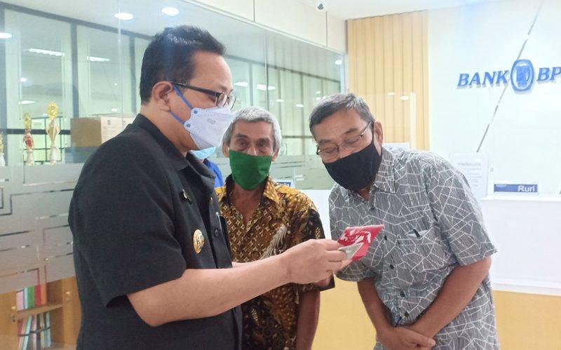 Heroe saat menyerahkan bantuan ASLUM secara simbolis di Bank BPD DIY di Mal Pelayanan Publik Balai Kota Yogyakarta, Senin (20/9/2021). (Foto:Humas Pemkot Yogya)
