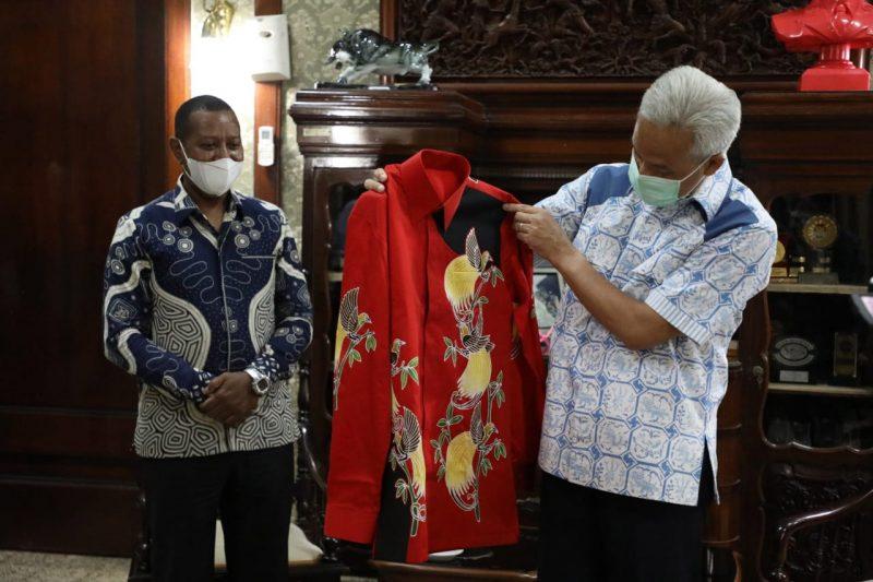 Rektor Universitas Cendrawasih Papua, Apolo Safanpo, memberikan sepasang batik bermotif burung Cendrawasih kepada Gubernur Jawa Tengah, Ganjar Pranowo.  (Foto: Humas Jateng)