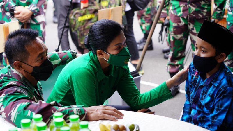 KSAD Jenderal TNI Andika Perkasa dan Ketua Umum Persit Kartika Chandra Kirana, Ny Hetty Andika Perkasa menyapa salah satu anak yatim piatu di acara bakti social. (Foto:Penrem072)