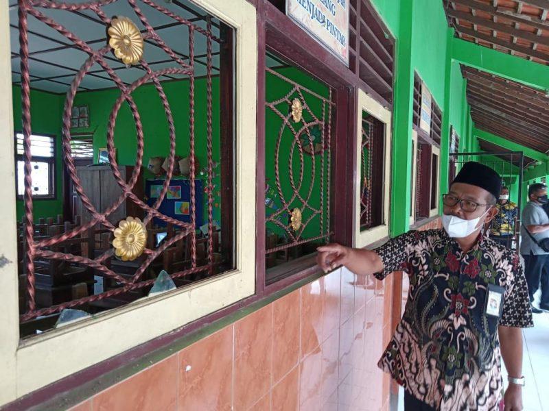 Kepala Sekolah SD N 2 Genengsari Kecamatan Wonosamodro Wahid Sri Wahyono menujukan jendela yang pecah. (Foto: Diskominfo Kabupaten Boyolali)