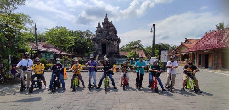 Para pelaku dan pegiat pariwisata saat mencoba sepeda elektrik dan scooter, dengan latar belakang Candi Pawon. (Foto: Humas/beritamagelang)
