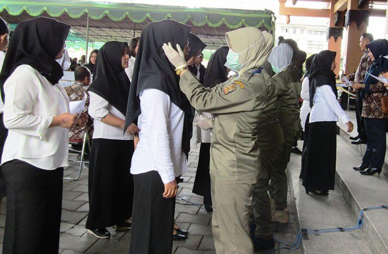 Petugas Satpol PP Kota Yogyakarta memeriksa peserta SKD CPNS Pemkot Yogyakarta pada tahun 2020 sebelum masuk ruang tes. (Foto: Humas Pemkot Yogya)