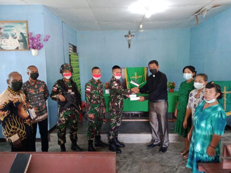 Prajurit 512/QY berikan Alkitab kepad jemaat gereja di Papua.  (Foto: Penerangan Yonif 512/QY)