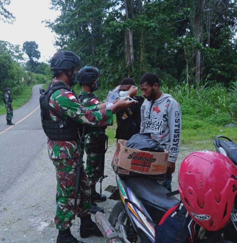 Prajurit Satgas Yonmek 512/QY bagikan masker kepada warga.  (Foto: Penerangan Yon 512/QY)