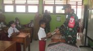 Pasiter Yonif 512/QY menyerahkan bantuan buku tulis kepada siswa SD Arso Pir. (Foto: Penerangan Yonmek 512/QY)