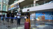 Peserta antre meninggalkan area bandara untuk menuju ke hotel karantina saat kegiatan simulasi penerbangan internasional di Bandara Internasional I Gusti Ngurah Rai, Badung, Bali, Sabtu (9/10/2021). Simulasi tersebut dilakukan untuk memastikan kesiapan petugas dan sarana prasarana serta menguji standar operasional prosedur dalam pelayanan penumpang penerbangan internasional di Bandara Ngurah Rai yang rencananya akan mulai dibuka pada 14 Oktober 2021 mendatang. (ANTARA FOTO/Fikri Yusuf/nz)