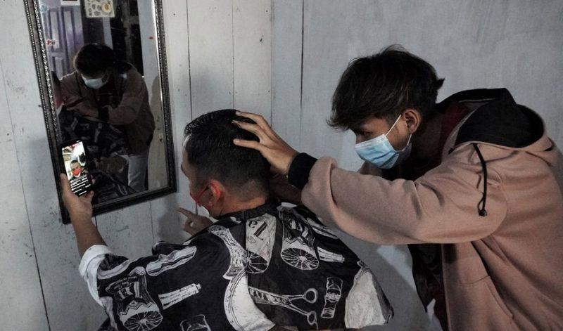 Bupati Batang Wihaji mencukur rambut di dalah satu warga yang disambanginya. (Foto: MC Batang)