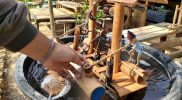 Seorang warga memegang bagian miniatur kincir air yang dipajang di obyek wisata pemandian air hangat Desa Nglobo, Kecamatan Jiken, Kabupaten Blora, Minggu (10/10/2021). Miniatur kincir air dibuat perajin setempat dari bahan bambu dan diminati pengunjung sebagai suvenir dan hiasan rumah dengan harga miniatur kincir air Rp150.000,00/buah. (Foto: MC Kab. Blora/Teguh)