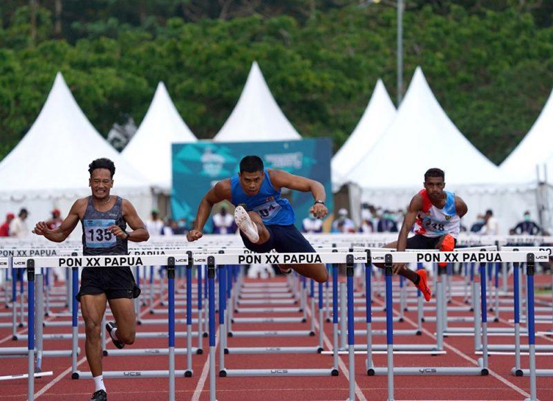Atlet 110 Meter Gawang Putra 304 RIO MAHOLTRA (BIRU) asal Sumatera Selatan berhasil finis terdepan dengan catatan waktu 14.11 mengungguli Hirzan Rahmadon (14.33) diposisi 2. 304 RIO MAHOLTRA (BIRU) berhasil meraih medali emas di lari 110 meter gawang putra. Timika. (Foto: Humas PPM/ Fernando Rahawarin)