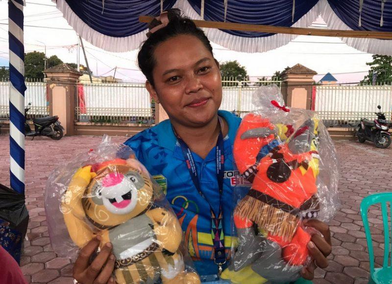 Pengelola Stand Blessing, Sitha menjual boneka maskot PON Kangpho dan Drawa. (Foto: Humasppm)