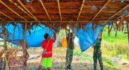 Prajurit Satgas Yonmek 512/QY berama masyarakat memasang atap jerami. (Foto: Penerangan Yonmek 512/QY)