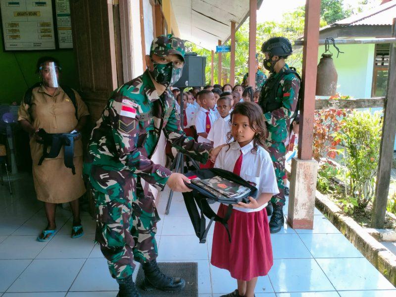 Prajurit Yonmek 512/QY bantu tas dan buku kepada siswa SD di perbatasan RI-PNG. (Foto: Penerangan Yonmek 512/QY)